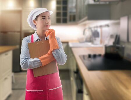 Woman maid presenting home cleaning services hand holding clipboard with blurred livingroom background Zdjęcie Seryjne