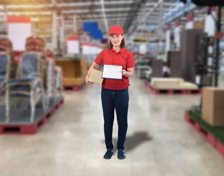 Female staff Delivering products Sign the signature on the product receipt form with parcel boxes Blurred the background of the warehouse