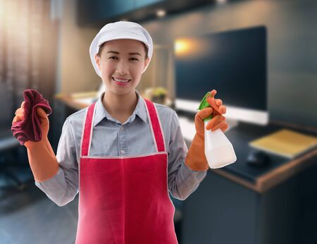 Cleaning concept Woman with bucket of washing fluids and rags in hands and cleaning equipment ready to clean house on blurred workingroom background
