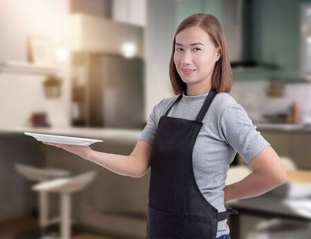 Female Chef assistant or housewife holding Kitchen equipment and blurred background kitchen
