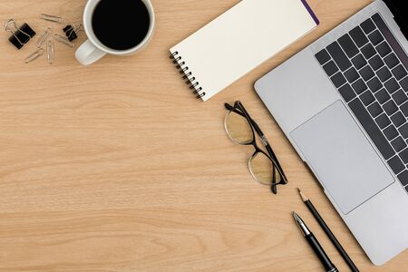 Top view Wood office desk table. Flat lay Workspace with eye glasses, coffee cup, laptop, paper clip, notebook, pen office supplies on wooden background