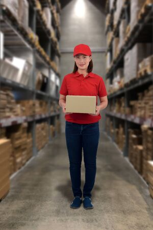 Female staff Lifting parcel boxes with Blurred the background of the warehouse storage Stok Fotoğraf