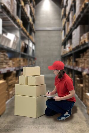 Female staff and parcel boxes checking stock or Preparing Goods For Dispatch and Blurred the background of the warehouse