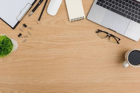 Top view Wood office desk table. Flat lay Workspace with eye glasses, coffee cup, tree pot, laptop, mouse computer, paper clip, notebook, clipboard, pencil, pen office supplies on wooden background Stok Fotoğraf