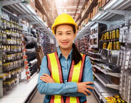 Portrait of Female staff warehouse operator with Blurred the background of Construction material on product shelf in store