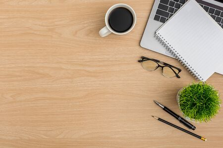 Top view Wood office desk table. Flat lay Workspace with eye glasses, laptop, tree pot, notebook, pen, pencil, coffee cup office supplies on wooden background Stok Fotoğraf