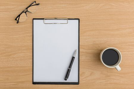 Top view office table desk. Flat lay Workspace with blank clipboard, pen, eye glasses, coffee cup office supplies on wooden table background.