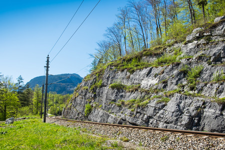 Railroad tracks have electric pole. The narrow-gauge railway along the ridge in clear blue sky day on summer