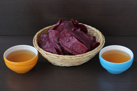Sweet potato chips with tea on wood background