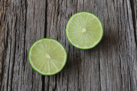 Lime with slices on wood background close up
