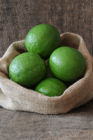 Fresh limes in small sack on wooden background