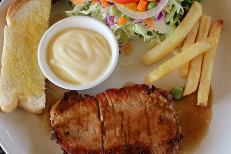 Pork steak with toast,vegetable salad and french fries