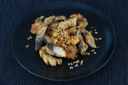 Deep-fried fish with garlic and pepper on black dish close up Archivio Fotografico