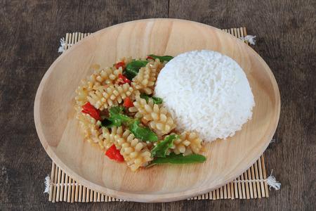 Thai food,stir fried squids with basil on wood background (Pad Ka Prao Pra Muek).This popular Thai dish serve with steamed rice .