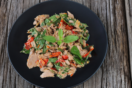 Thai food,stir fried with tuna and basil(Pad Ka Prao tuna)on wooden background,homemade meal.
