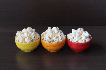 Popcorn in three color cups on wood background