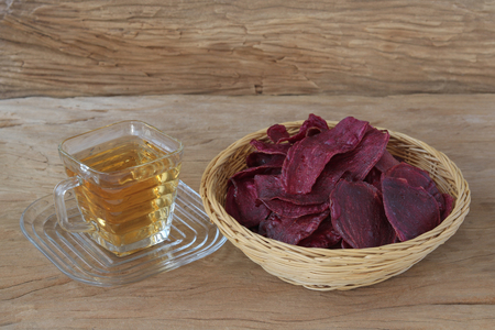 Tea with sweet potato chips on wood background
