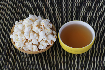 Popcorn and tea on reed mat background Archivio Fotografico