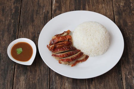 Roasted duck with steamed rice on wooden background