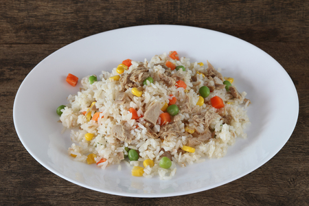 Fried rice with tuna and vegetables on wooden background close up