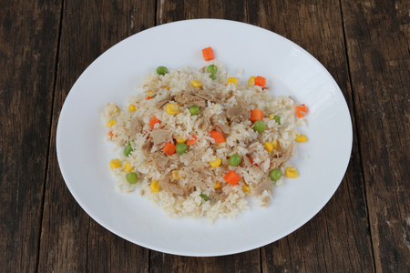 Fried rice with tuna and vegetables on wood background