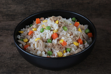 Fried rice with tuna and vegetables on wood background close up,homemade meal Archivio Fotografico