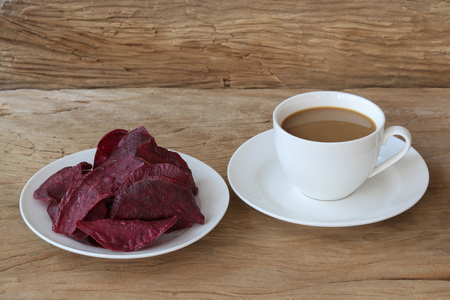 Sweet potato chips with coffee on wood background Archivio Fotografico