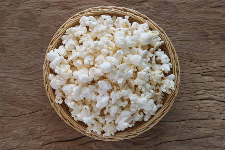 Popcorn in a basket on old wooden background