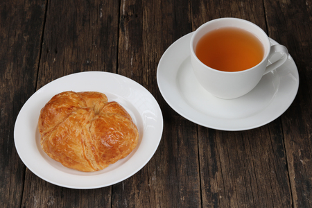 Croissant with tea on old wooden background
