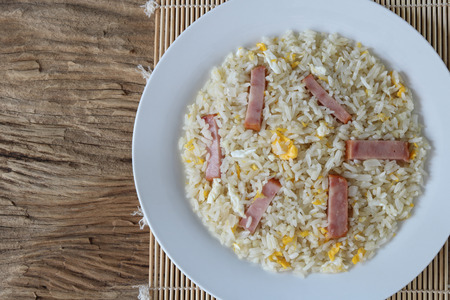 Fried rice with bacon and egg on old wooden background