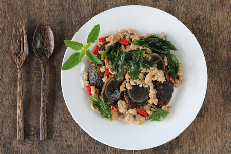 Stir fried preserved egg with crispy basil ( Kai Yiew Ma Kra Prao Krob ).This popular Thai dish serve with steamed rice.Top view