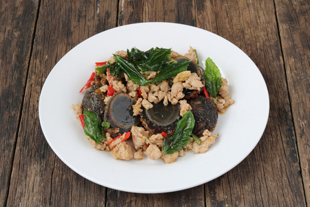 Stir fried preserved egg with crispy basil ( Kai Yiew Ma Kra Prao Krob ).This popular Thai dish serve with steamed rice.