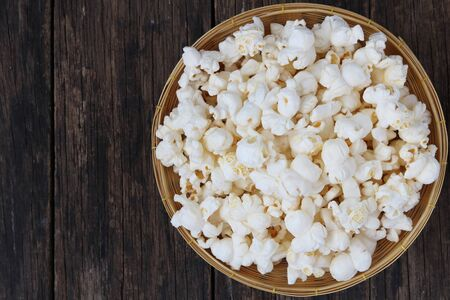 Popcorn in basket  on wooden table close up Archivio Fotografico