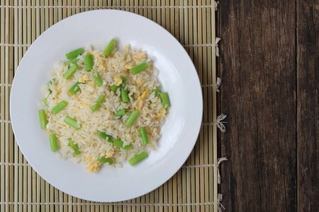 Fried rice with asparagus and egg on wood background top view Archivio Fotografico