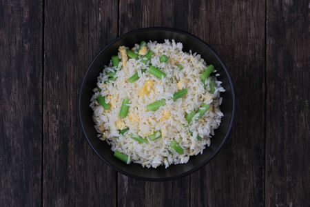 Fried rice with asparagus and egg in black bowl top view Archivio Fotografico