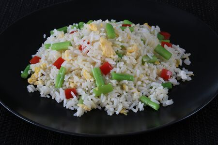 Fried rice with asparagus and egg in black dish close up Archivio Fotografico