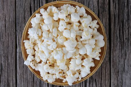 Popcorn in basket  on old wooden background close up Archivio Fotografico