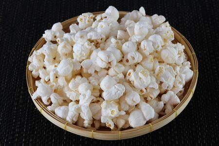 Popcorn in basket  on black background close up