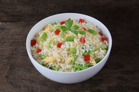 Fried rice with asparagus and egg on wood background