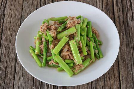 Stir fried tuna and asparagus on old wood blackground Archivio Fotografico