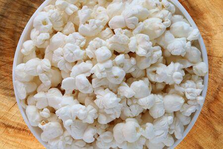 Popcorn in a white bowl on wooden background close up Archivio Fotografico