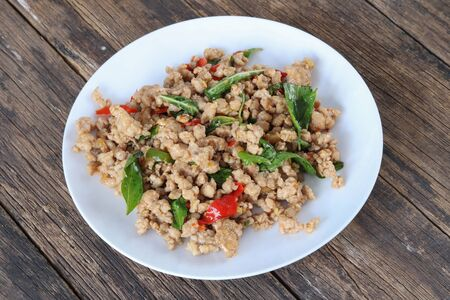 Stir fried minced pork with basil on wood table.This popular Thai dish serve with steamed rice.Homemade meal