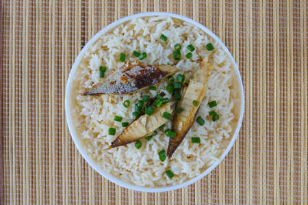 Fried rice with mackerel top view on mat background