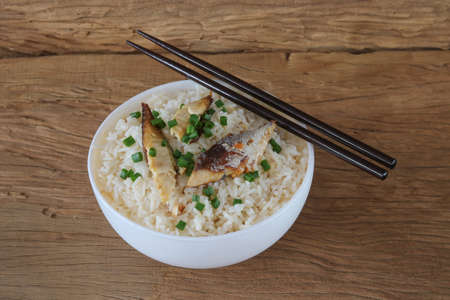 Fried rice with mackerel on old wooden background Archivio Fotografico