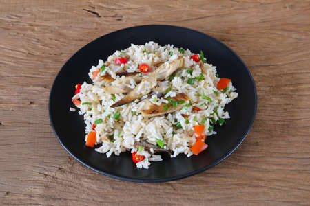 Fried rice with mackerel in black dish on wooden background