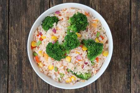 Fried rice with broccoli and corn on old wood background top view Archivio Fotografico