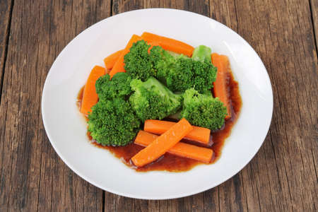 Stir fried broccoli and carrot on old wooden background Archivio Fotografico