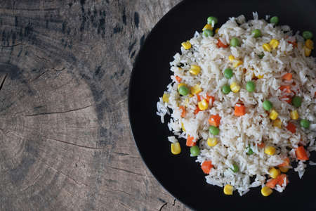 Fried rice with vegetables on old wood background Archivio Fotografico
