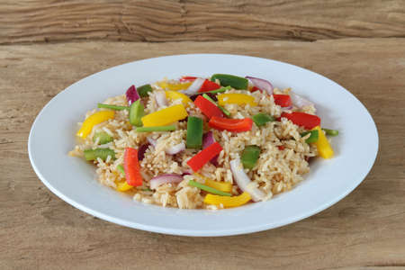 Fried rice with sweet pepper on old wooden background.Homemade meal for good health Banco de Imagens