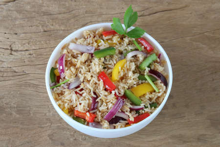 Fried rice with sweet pepper on old wooden background.